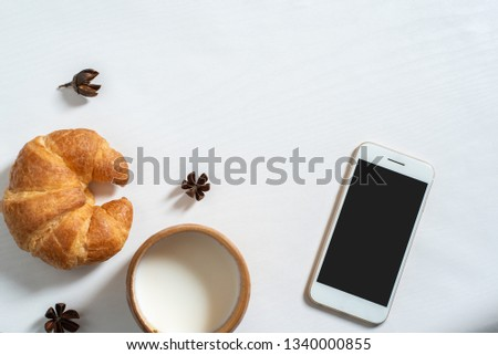 Top view of cupp of milk, note book, croissant on wooden table. Workspace for writing , draft, sketch, on the morning Stok fotoğraf ©