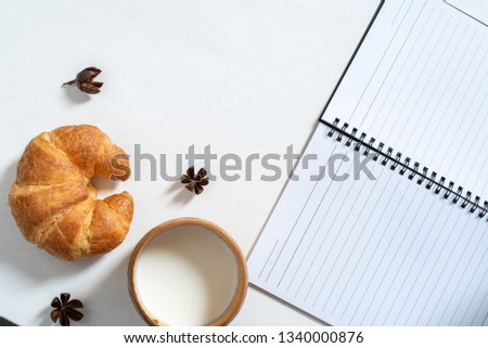 Top view of cupp of milk, note book, croissant on wooden table. Workspace for writing , draft, sketch, in the morning Stok fotoğraf ©