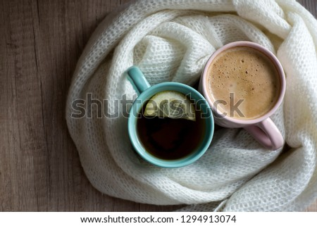 Top view of Cups of hot coffee or cappuccino and hot tea with lemon. Warm scarf a on wooden table. Good morning. Winter mood concept. Warm autumn or winter picture. Time for relax. Coffee vs Tea. Love