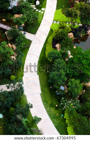 top view of curve brick path in garden, and surrounded by green plants.