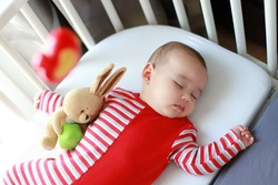 Top view of cute baby boy sleeping in cot with mobile toy.Mixed race Asian-German infant lying in sleeper crib attached to parents bed. Child day sleep.