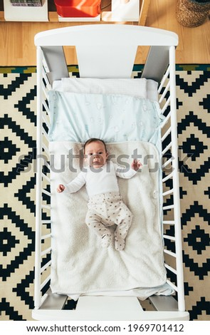 Top View of Cute Baby Looking at Camera and Lying in Crib . Portrait of a little baby boy waking up in his crib in the morning. Foto stock ©