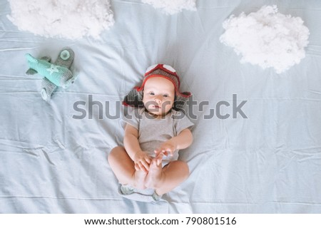 top view of cute infant child in knitted pilot hat with toy plane surrounded with clouds made of cotton in bed