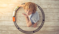 Top view of cute little boy playing with toy train, looking at camera and smiling