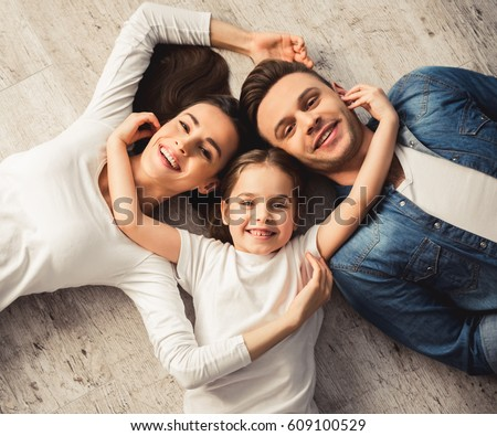 Top view of cute little girl and her beautiful young parents looking at camera and smiling while lying on the floor at home