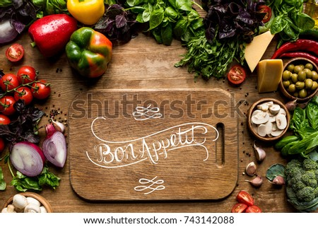 top view of cutting board, fresh vegetables and herbs on wooden tabletop