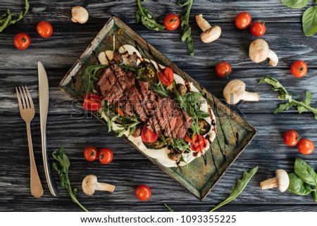top view of delicious roasted steak, fork with knife and vegetables on wooden table  #1093355225