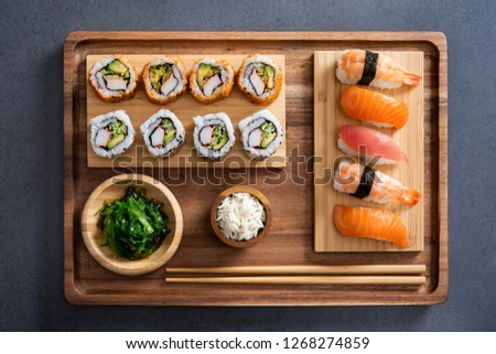 Top view of delicious variety sushi pieces setting on wooden tray. High angle view of japanese food with huramaki, maki, rolls, nigiri, seaweed and rice in a bowl. Flat image of fresh japanese sushi.