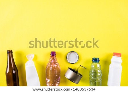 Top view of Different garbage materials for recycling on yellow background. Recycle, environment and Eco concept