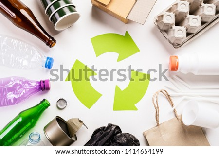 Top view of Different garbage materials with recycling symbol on white wooden table background. Recycle, World Environment Day and Eco concept #1414654199