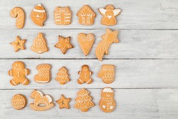 Top view of different shapes of nicely decorated gingerbread Christmas cookies on white wooden background