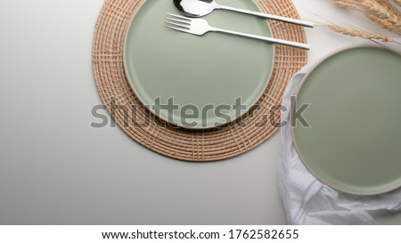 Top view of dinning table with mock-up turquoise ceramic plates and silverware on placemat and napkin on white table Stock photo ©