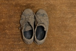 Top view of dirty dried muddy and messy sneaker shoes totally covered with mud looking unrecognizable while laying on a brown coco doormat