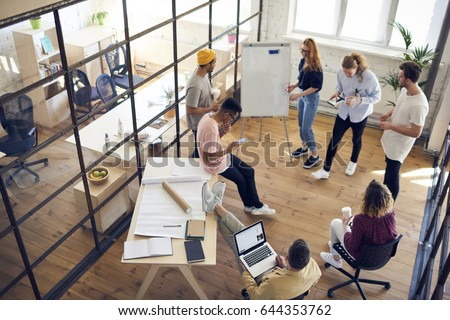 Photo of Top view of diversity group working together on architectural project in office interior,young male and female creative graphic designers collaborating during brainstorming using modern technology