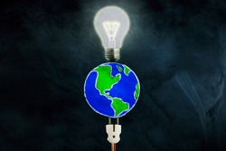 Top view of drawn earth planet with electric plugs and bright bulb on the chalkboard background