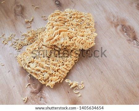 Top view of dried  instant noodles or instant ramen on wooden table.