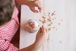 top view of Easter cake decorate children's hands with decorative dusting. Easter cake in the hands of a child on the background of a white wooden table.