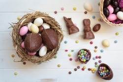 Top view of easter edible eggs on nest, chocolate rabbits and sweets on white wooden table