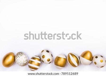 Top view of easter eggs colored with golden paint in differen patterns. Various striped and dotted designs. White background. Copy space.