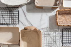 Top view of empty closet organization boxes and steel wire baskets in different shape placed on white marble table with copy space. Marie Kondo's hikidashi boxes for tidying clothes and drawer storage