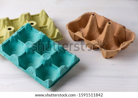 Top view of empty egg cartons, green, brown and yellow on white wood, ready for recycling