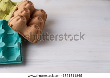 Top view of empty egg cartons, green, brown and yellow on white wood, ready for recycling, horizontally with copy space