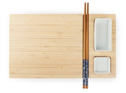 Top view of empty wooden bamboo sushi board with chopsticks and saucer. Food design element isolated on white