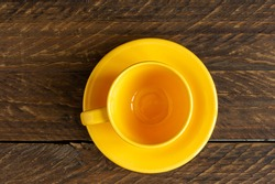 Top view of empty yellow cup and saucer on wooden rustic bckground. Kitchen crockery.