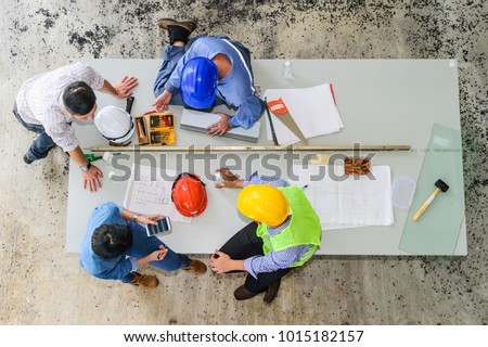 Top view of engineering team, site manager, field engineer and foreman looking at constructed paper blueprint plans at construction site. Business Concept for team work of heavy industry.