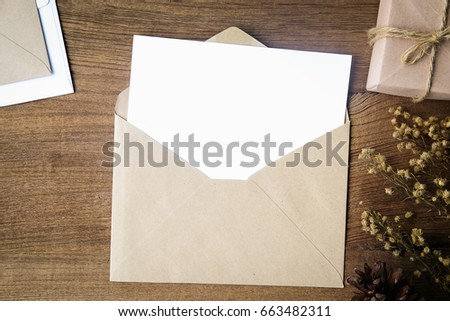 Top view of envelope and blank greeting card with rose flowers on white wooden background. #663482311