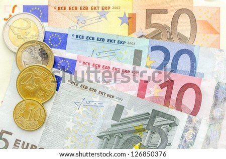 Top view of Euro coins on banknotes.