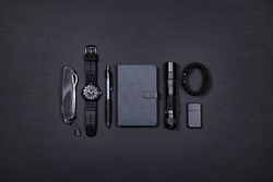 Top view of everyday carry (EDC) items for men in black color - folding knife, lighter, note book, tactical pen, watch, paracord survival bracelet and flashight. Flat lay. Minimal concept.