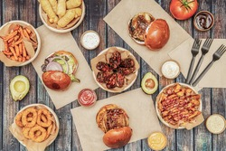 Top view of fast food dishes, bbq chicken wings, assorted beef burgers, onion rings, tequeños, potatoes with sauces and avocado