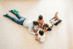 Top view of father and children lying on carpet and painting doodles. Caucasian dad drawing with markers and playing with lovely kids at home. Childhood, game activity and fatherhood concept
