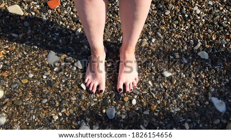 Top view of feet at the beach with sea waves. Concept. Connecting to nature, beautiful legs and feet of a woman with her nails painted black being washed by sea or ocean waves.