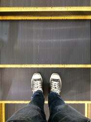 Top view of feet in sneaker shoes on escalator steps,copy space.
