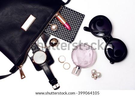 Top view of female accessories for woman. Trendy black sunglasses, black handbag , watch , lipstick , perfume , rings , smart phone