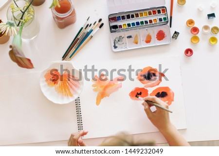 Top view of female artist making abstract watercolor sketches. Stylish artistic workspace.