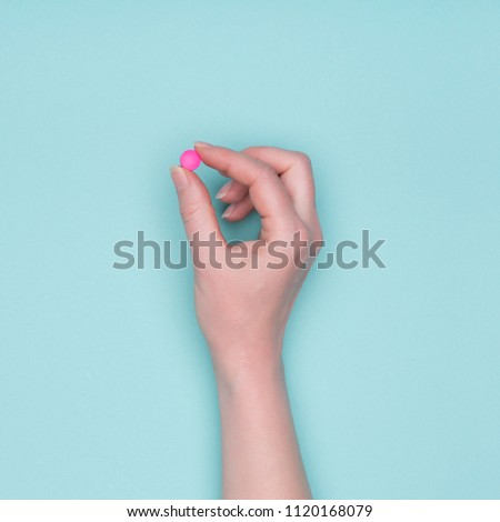 Top view of female hand holding pink prescription pill over pastel blue background. Sick patient taking medication. #1120168079