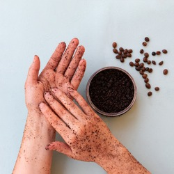 Top view of female hands and a jar with roasted coffee bean scrub and sea salt on mint background in square format. Rejuvenating scrub in round jar for skin exfoliation.