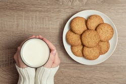 Top view of female hands holding a glass of milk, with plate of chocolate chip cookies placed next to it on the table