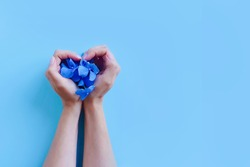 Top view of female hands with hydrangea flowers on blue background. Heart and love symbol. Fashion art and beauty flatlay, colored shadows. Concept hand care