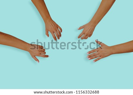 Top view of female hands with nails on a blue, pastel background. Female hands reach for something in the middle of the table. The concept of desire, the desire to receive something. #1156332688