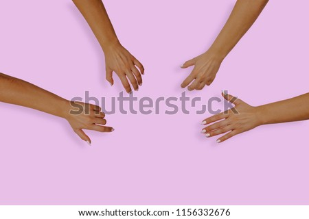 Top view of female hands with nails on a pink, pastel background. Female hands reach for something in the middle of the table. The concept of desire, the desire to receive something. #1156332676
