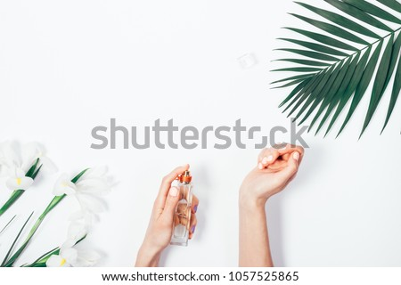 Top view of female hands with pink manicure spraying perfume on wrist among the palm branch and iris flowers on white background. Stylish flat lay frame with copy space for text. #1057525865