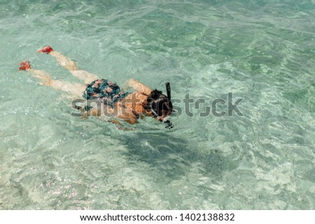 Top view of female swimmer snorkeling in sea. Snorkelling - woman wearing diving mask and snorkel swimming in water on hot sunny day. #1402138832