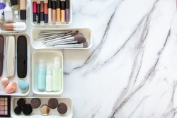 Top view of female visagiste is neatly placing cosmetic and vanity items in MUJI's PP makeup storage boxes with various sizes on white marble dressing table. Decluttering and organization concept.