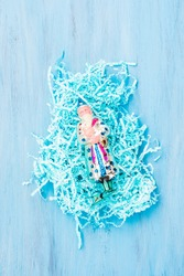 Top view of festive tinsel decoration and old christmas tree toy on it. Antique santa claus toy on blue pastel background. Festive christmas backdrop. New year and winter holiday concept