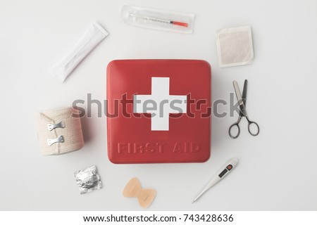 Top view of first-aid kit with medical supplies around