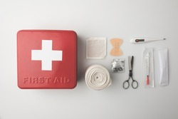 Top view of first-aid kit with patch, scissors, thermometer and elastic bandage